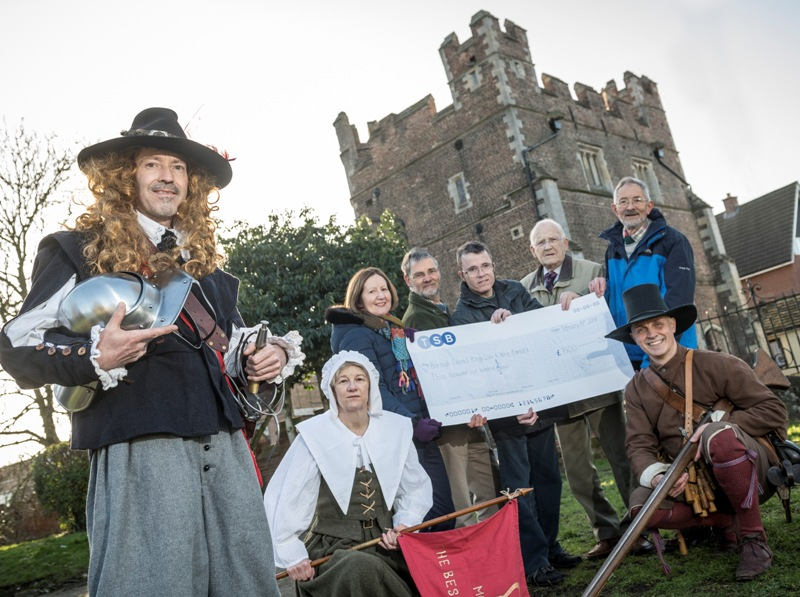 Friends of The Walks present a cheque to Cllr Nockolds in front of the South Gate, accompanied by characters in medieval costume
