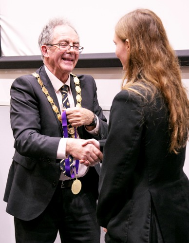 The Mayor hands out a medal.