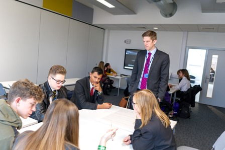 A group of students work on a problem at the West Norfolk University Challenge Conference 2018, watched by a teacher