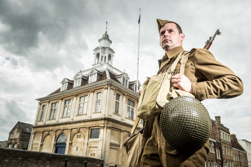 a man dressed as a 1940s soldier in front of the custom house with a cloudy sky