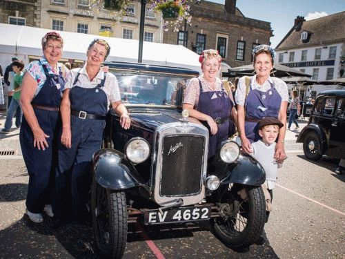 4 female munitions factory workers by a vintage car in the Tuesday Market Place