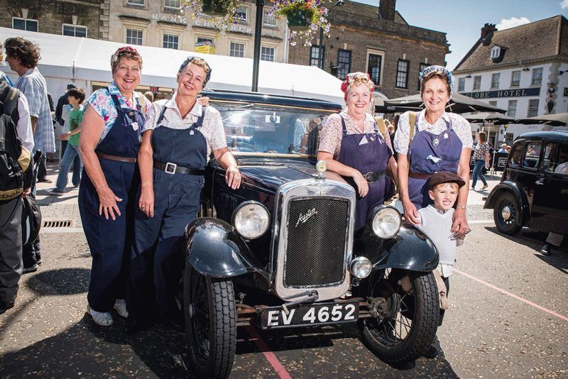 Four female factory workers pose in front of a vintage car in the sunny Tuesday Market Place.