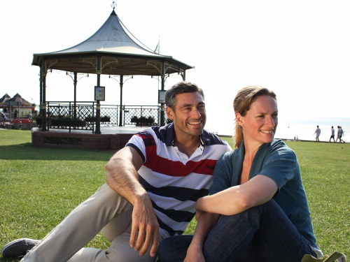 An image of two people sitting in front of the Bandstand on The Green at Hunstanton