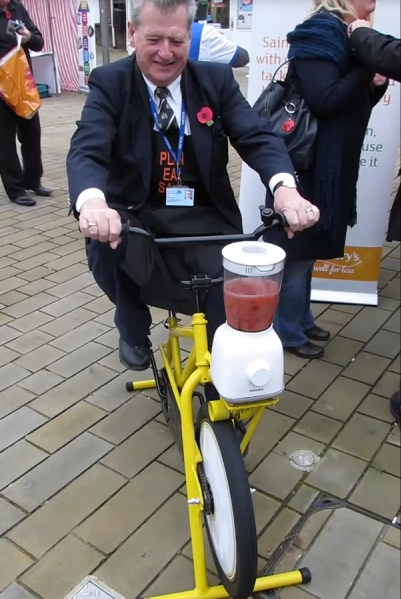 Cllr Ian Devereux is pictured operating a smoothie maker powered by pedalling a bicycle, in Downham Market market place