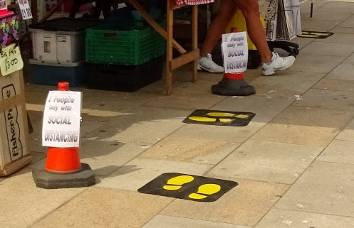 King's Lynn Market with footsteps that display a 2 metre distance and a limit to how many shoppers at a time.