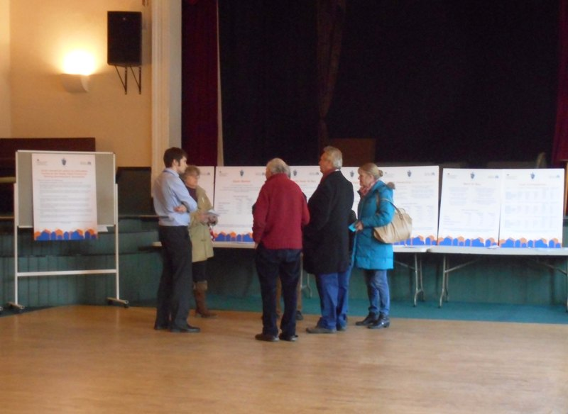 Members of the public examining information boards about the Sheep Field Community Housing Development, in Hunstanton Town Hall