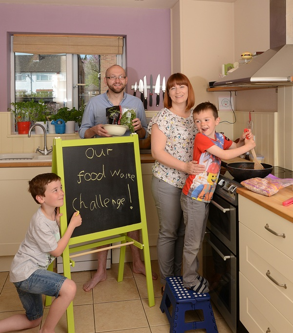 "A family cooking in a kitchen next to a chalkboard saying ""our food waste challenge"""