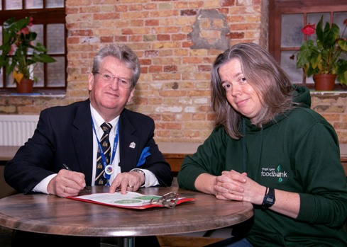 Cllr Devereux signs the Courtauld agreement, watched by Helen Gilbert from King's Lynn Foodbank