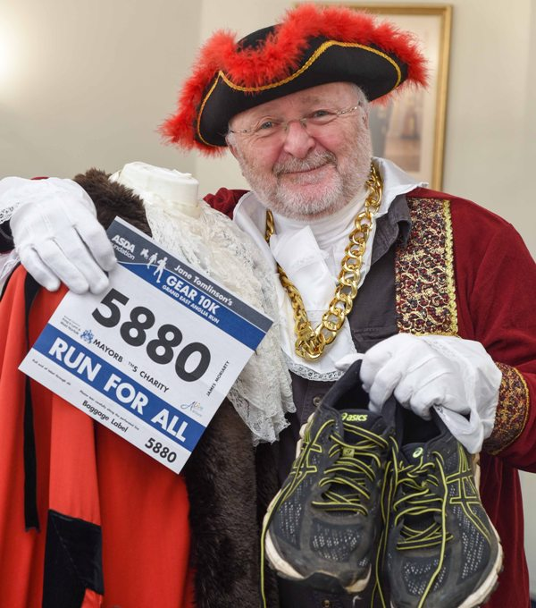 Cllr Jim Moriarty, deputy mayor of King's Lynn & West Norfolk in 2017/18 holding his GEAR race number and running shoes, dressed in his mayoral robes.