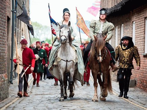 A man and a woman on horseback in medieval dress, with other people walking, in a parade through Lynn's cobbled riverfront streets