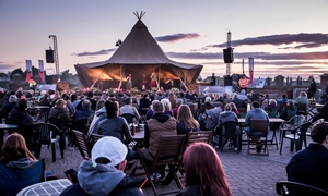 A crowd watch live music on King's Staithe Square as the sun sets at the Hanse Festival