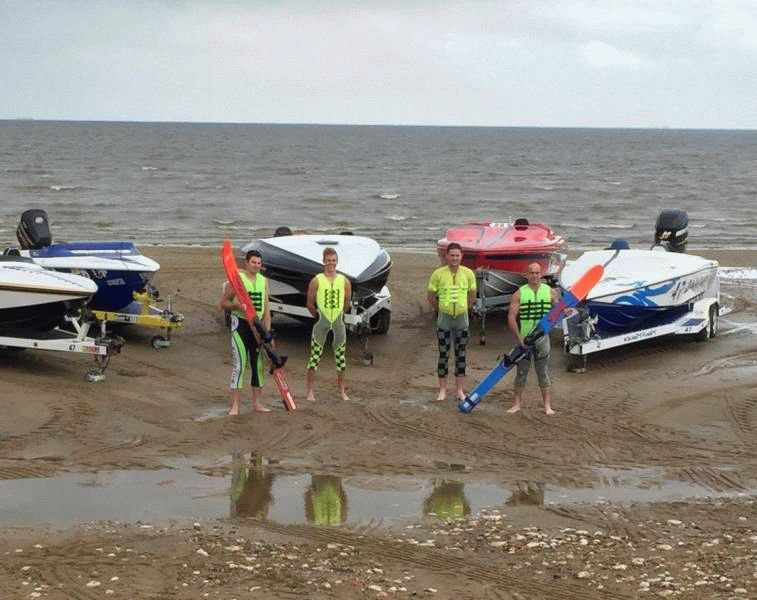Members of the Hunstanton Ski Club stand in front of speed boats on the beach, dressed in their skiing gear, holding skis.