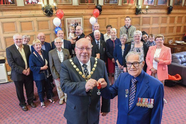 Harry Bowdery is presented with his medal by the mayor, with his family standing behind to watch, in the mayor's parlour.