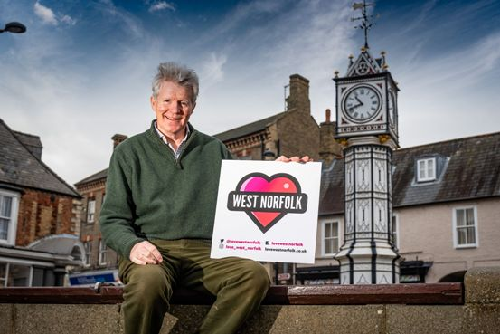 James Bagge outside the Clock in Downham Market with the Love West Norfolk logo.