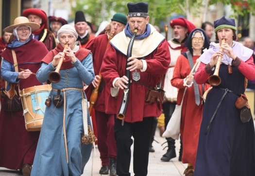A group of musicians dressed in medieval costume walking through the centre of King's Lynn