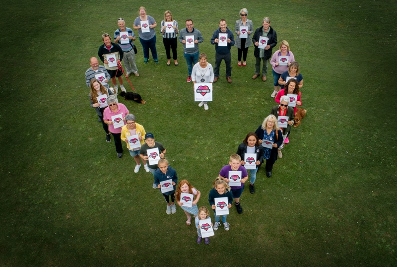 A group of people viewed from above standing in the shape of a heart, holding Love West Norfolk placards