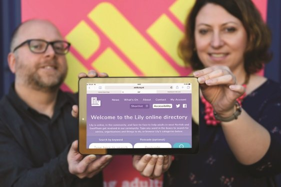 An image of two people involved in the re-launch of the LILY website holding a tablet displaying the new website