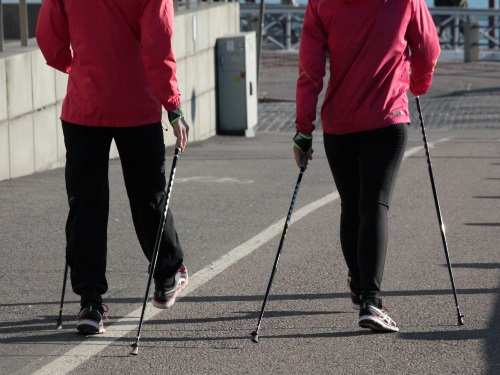 A picture of two people walking while using walking poles