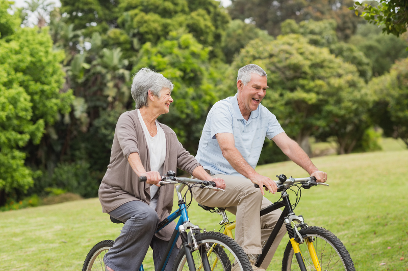 An older couple cycle together in a park