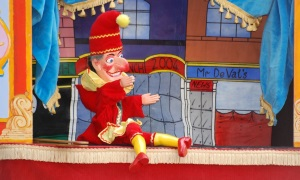 A picture of the character punch on stage in a punch and judy show