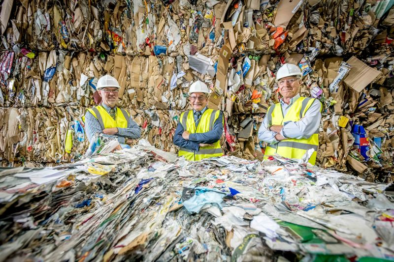 three middle-aged white men in hard hats and hi-vis jackets stand surrounded by recycling. They look pleased.
