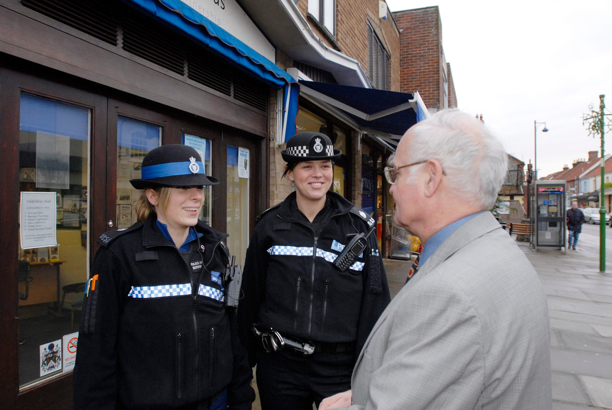 A PCSO and a police officer chat in the street to an elderly gentleman