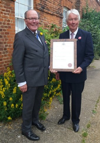 Sir Jeremy Bagge on the left gives Sir Richard Jewson on the right the freedom of west Norfolk certificate.