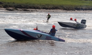 Two powerboats pulling water skiers in the River Ouse