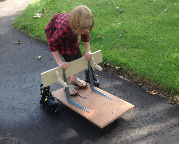 A small child rides on the beginnings of a soap box kart under construction