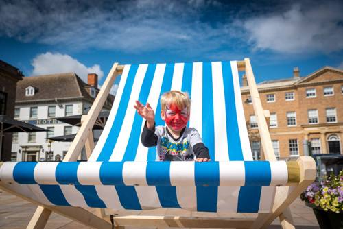 Child sitting on a giant deckchair in the Tuesday Market Place.