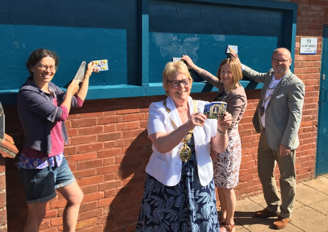 Kate Dunbar, Cllr Carol Bower, Cllr Elizabeth Nockolds, and Cllr Adrian Winnington laying hand-painted ceramic tiles on the toilet block windows in the Hunstanton Heritage Gardens