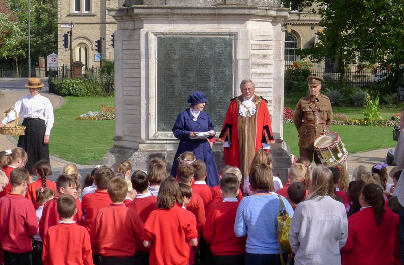 Cllr Daubney, Rachael Williams from Stories of Lynn and costumed characters talk to a crowd of schoolchildren in front of the war memorial in tower gardens in King's LYnn on a sunny day