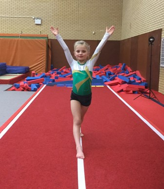 a child in a gymnastic pose on a newly-installed tumble track
