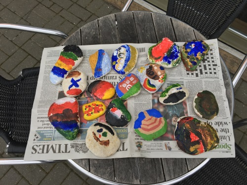 An image of painted stones lying on a newspaper on a table
