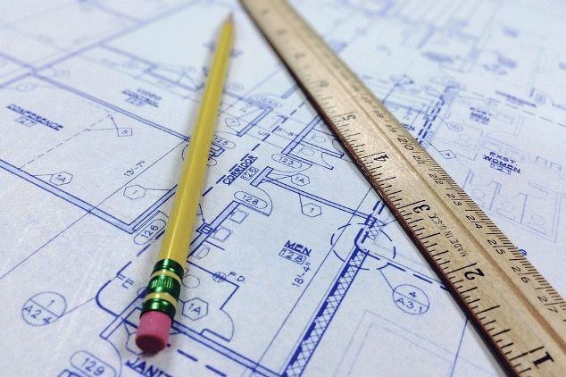 A blueprint of a house with a ruler and pencil lying across it.