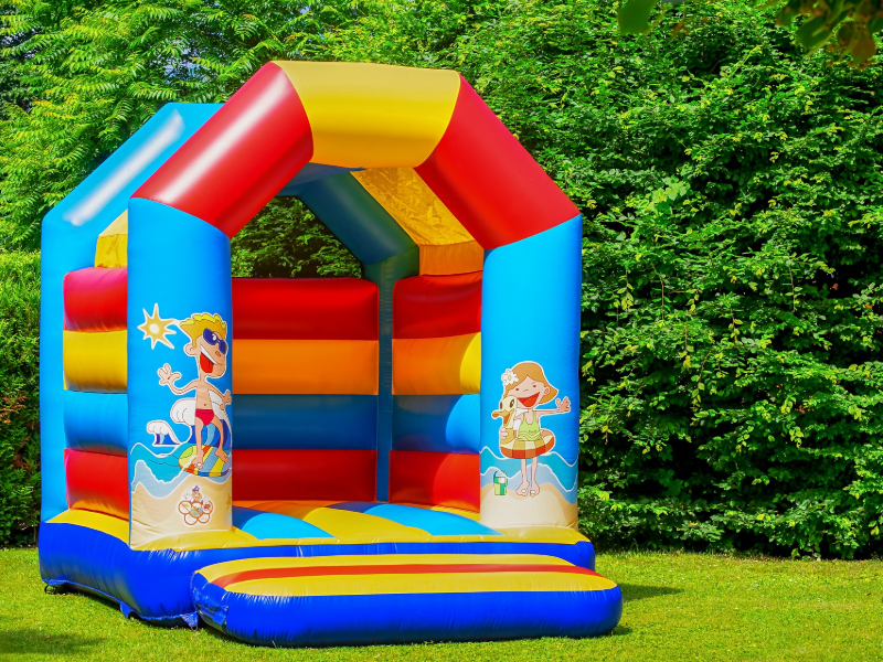 A bouncy castle on grass in gront of a hedge