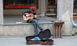 An image of a busker in the street playing their guitar