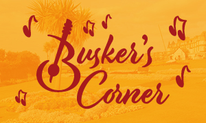"A poster with the words ""Busker's Corner"" written on it to advertise the music event in the Hunstanton Heritage Gardens"
