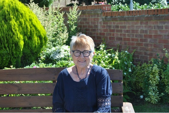Cllr Susan Fraser sitting on a bench in a garden