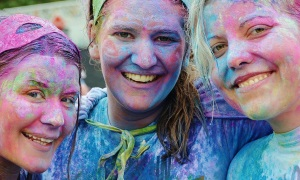 An image of three smiling people with paint on their face