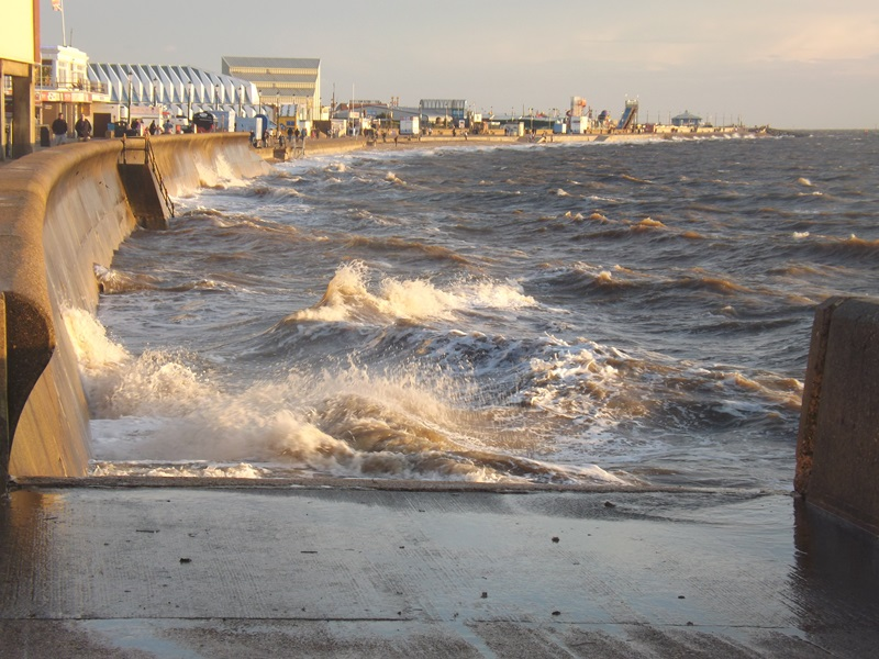 A view of waves crashing against the concrete promenade in Hunstanton on a sunny day