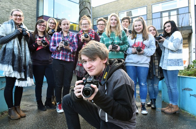 A group of young people holding cameras, all part of the Kick the Dust project