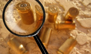 An image of a magnifying glass looking at a bullet from a gun at a crime scene