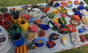 A picture of many colourful painted pebbles drying on a table