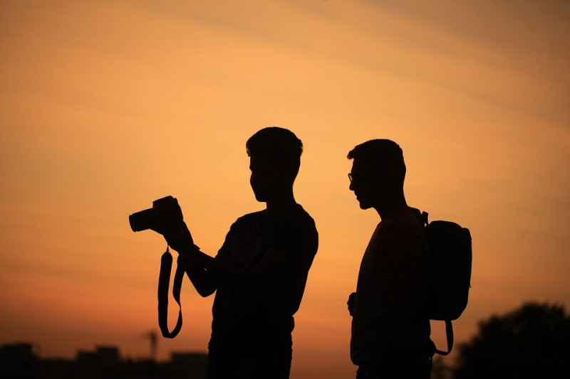 Two men in silhouette against a sunset. One is holding a camera.