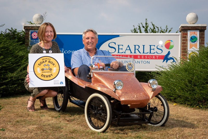 Cllr Elizabeth Nockolds crouching beside a soap box kart holding a board with the new soap box derby logo. Paul Searle is sitting in the soap box kart.