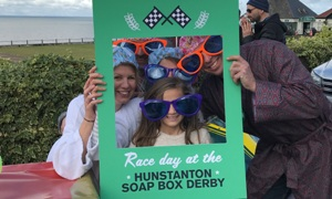 A family in oversized sunglasses pose for a photo holding the Hunstanton Soap Box Derby selfie frame