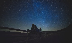 An image of people sitting on a fence gazing up at the stars at night
