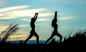 An image of two people performing gentle yoga type exercise outside at dusk